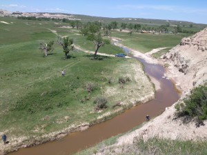 Students and faculty in the PEEC program lead local Native American high school students (note school bus in upper right portion of photo) on a field excursion to discuss stream health and the influence of geologic formations on water quality. Eroding sedimentary deposits such as this contribute suspended sediment to surface water in the stream.